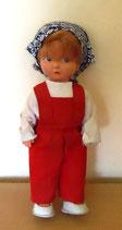 Kleine Puppe mit roter Latzhose und Kopftuch