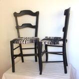 Une paire de chaises paillées assorties. Boiserie peinte en noir. Dégradés de noir, taupe et gris sur l'assise.