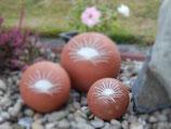 Tierurne in Kugelform in terrakottafarben mit Sonnenmotiv