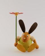 Hase mit Blume sitzend