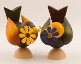 Vogel mit Blume im Schnabel