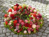 Trauerkranz mit Rosen rundumgesteckt, bunt