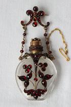 Boheems kristallen parfumflesje met vergulde ornamenten bezet met granaten, als broche.