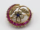 18 Karaat gouden broche met diamanten, robijnen en saffier,  rond met bloem.