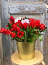 Cubo repleto de tulipanes rojos