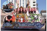 【山車×自動車メーカー】2tトラック平車に装飾した祭り用山車。 イラストのパーツを重ね貼りするシャドーアートで立体感が生まれ迫力が増しました。 荷台には人が乗れるようステージを設置。イルミネーションも施しました。