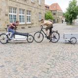 Lastenrad und Lastenanhaenger versuchen sich gegenseitig weg zu schieben