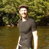 Mann steht in Badehose, schwarzem, nassem Shirt und Muetze im Wasser