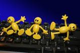 3 kleine gelbe Mänchen arbeiten auf der Tastatur