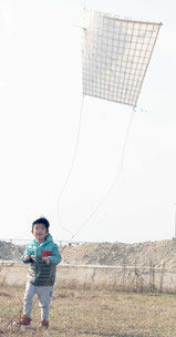 揚がっていく凧を見上げる子ども=11日午前、南ぬ浜町新港地区