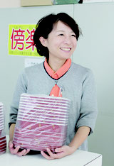 検品した食品容器を店頭に並べる知名恵子さん=まるわ包装