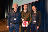 Michael Hebeisen from Lausanne receiving the immunomonitoring poster prize at CIMT 2014, Mainz, from the judges S. Janetzki and G. Pawelec