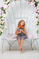 Mädchen mit Blumen auf einer Art Thron