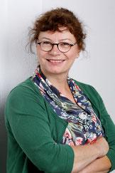 Bettina Lohmüller, Inhaberin, Frau mit dunklen Locken und Brille, bunte Bluse und grüne Strickjacke