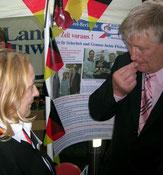 Vor Plakaten und schwar-rot-goldenen Fähnchen: Landwirtwirtschaftsminister Ehlen und Helga Karl im Gespräch. Foto: (c) Helga Karl
