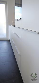 Aluminium Griffleiste auf weißer Front für Küche mit Insel in weiß mit Keramik-Arbeitsplatte u. indirekt beleuchteter Nischenplatte mit Steckboard Backofen von Siemens u. Liebherr Kühl-Gefrierkombination im Highboard verstaut, Kücheninsel weiß
