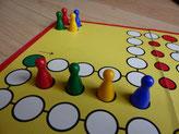 Foto eines Mensch-Ärgere-Dich-Nicht-Spiels, als Zeichen der Inklusion stehen vier verschiedenfarbige Figuren in einem Haus