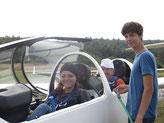 Schnupperschülerin Clara freut sich auf den Flug im doppelsitzigen Ausbildungsflugzeug mit Fluglehrer Johannes Bick. Valentin (rechts) hilft bei der Vorbereitung für den Windenstart.