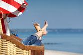 Frau entspannt im Strandkorb am Strand