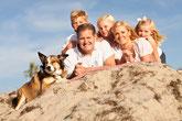 Glückliche Familie mit Kindern und Hund am Strand