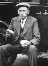 Jan Willem Bembom, een broodje etend, zittend op de treeplank van een auto (Jaren '20).
