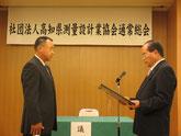 橋口会長から長年の功績を表彰される理事の細木俊輔氏