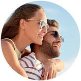 Eine Familie sitzt auf einem Auto und alle strecken die Hände nach oben. Gut versichert mit einer Corona-Zusatzversicherung im Urlaub.