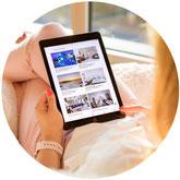 Eine Frau schaut in ihr Tablet für Urlaubsbuchungen. Sie will als Kooperationspartner ihren Kunden Reiseversicherungen anbieten.