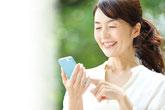 スマートフォンを見ながら笑顔の女性