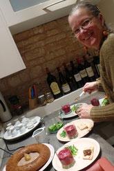Chantal en cuisine présentant les assiettes de mousse de betterave et un baba au cognac en 1er plan
