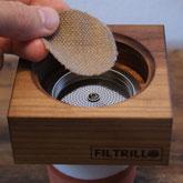Hand legt runden Einlegefilter in Kaffeefilter aus Holz.