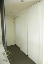 Vorratsraum mit weißer Hochglanz Schiebetür und flächenbündig integrierten Kühlschrank mit