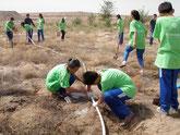 ホースで木に水をやる子どもたち