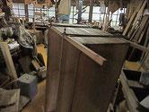 桐たんすの側板の割れをハタガネにて圧力をかけ修理しています。