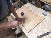 水屋戸棚の引戸戸板を枠にはめ釘を打って固定しています。