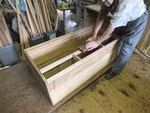 桐箪笥の胴縁と棚板に鉋をかけ新しい桐をはめ面を作っています。