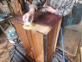 時代箪笥本体の表面に塗ってある塗料をサンダーでかき取っています。