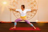 """Eine Frau steht in Yoga-Position vor einer goldenen """"Blume des Lebens""""."""