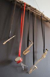 Querflöte - Trommel - Saxophon - Zugposaune  und Trompete an Seidenbändern an Treibholzästen in verschiedenen Höhen aufgehängt.