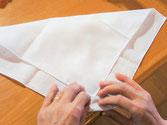 2 綿を適量、ハンカチ中央において、折りたたみます。