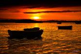 Bateaux au mouillage devant le couché de soleil, la lumiere orangée envahit la mer.