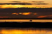 Dans les reflets du couchant, un bateau rentre du banc d'arguin vers le port sur un tapis de feu