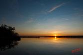 Ciel bleu sur le lac de Souston, au fond le soleil rejoint son reflet dans l'eau calme