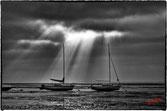 Deux voiliers a maréé basse, sur le bassin d arcachon, eclairés par la lumiere filtée par les nuages
