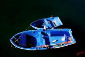 Un petit bateau amaré à un plus grand, sur une eau sombre