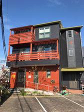 3階建て茶色の外観にオレンジの看板が目印
