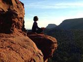 Sur un rocher une silhouette de méditant se détache sur fond de ciel
