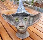 Waldelf mit großen Ohren und goldenen Augen schaut einen an. Keramik Unikat