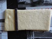 Разрезать тесто на прямоугольники основой в 8 см и высотой в 16 см. Положить маленький кусочек  шоколада  (8 см на 2 см)