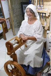 Isabelle filant la laine au rouet lors des médiévales.